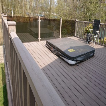 Mocha decking with glass panels built around hot tub