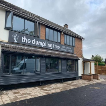 Tarmac surfacing, composite cladding, patio restoration, dwarf walling and simple pergola to support make the front of a new restaurant more attractive